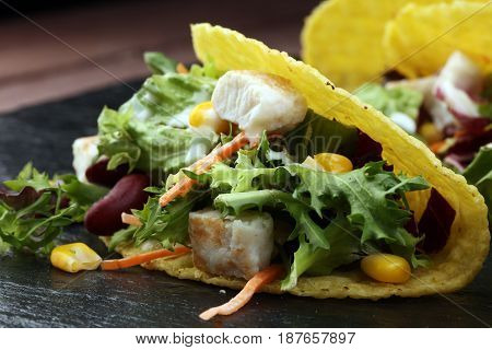 three mexican salat carnitas tacos on black stone