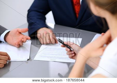 Business lady offering businessman black pen for signing a contract.
