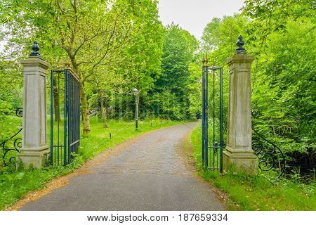 Driveway of an estate between an opened wrought iron gate between two stone pillars