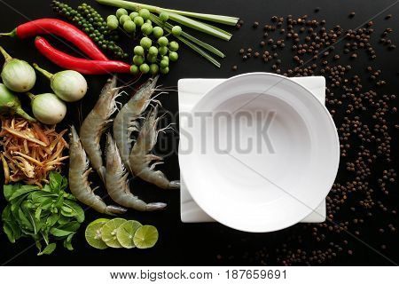 Ingredients for cooking with a white plate on wooden rustic background top view close up