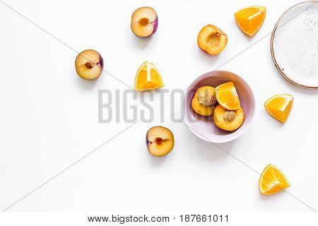 woman summer breackfast with orange and peach fruits on white desk background flat lay
