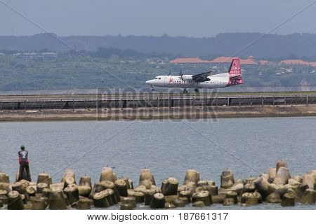 BALI - April 3 2016: Wings TransNusa airlines is a low cost Indonesia airline and a schedule commuter passenger airline based in Jakarta Indonesia. Plane lands on the runway at the airport in Bali.
