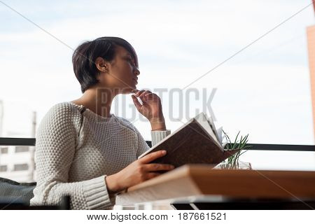 Side view of elegant woman sitting at table in outside cafe with book and looking away.