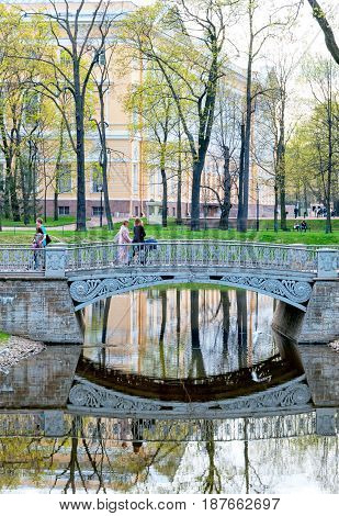 SAINT - PETERSBURG, RUSSIA - MAY 18, 2017: People on the bridge over the pond in The Mikhaylovsky Garden next to The Mikhaylovsky Palace (Russian Museum)
