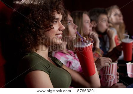 International friends, stylish girls and boys watching new movie at cinema, spending time together, eating tasty popcorn. Pretty woman with volumed curly hair drinking cola, looking at screen.