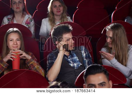 Front view of group of people watching film in cinema hall, brunet man talking at call phone, angry and shocked woman gesturing by hand stopping him. Leisure and culture of young girls and boy.