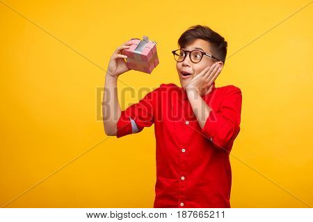 Young expressive boy receiving a gift and feeling surprised on the yellow background.