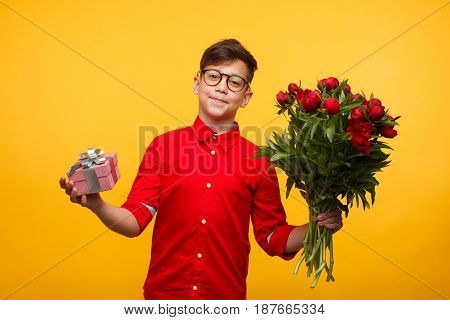 Young boy with small gift box and big bunch of flowers on the yellow background.