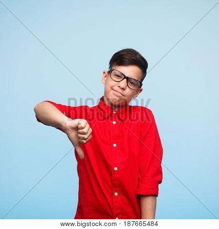 Young teen looking at camera with thumb down expressing disagreement on the blue background.