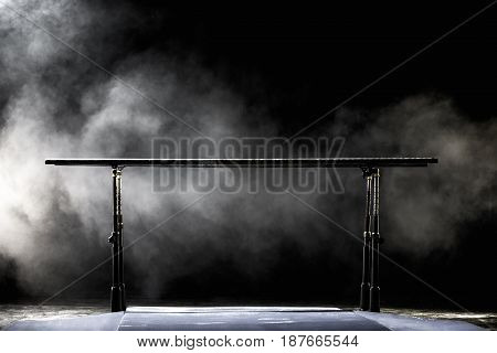 Gymnastic parallel bars. On black background with fog.