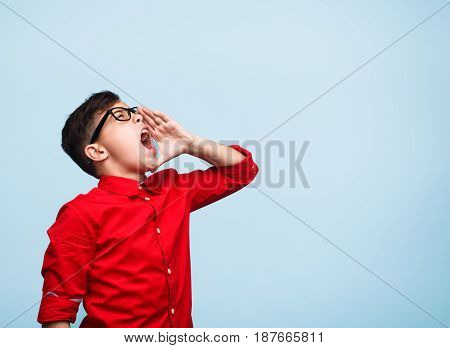 Horizontal studio shot of young male teen in glasses holding hand to mouth and yelling.