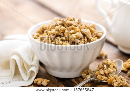 Granola in bowl on wooden table closup