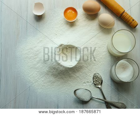 Baking cake in the rustic kitchen. Ingredients of the dough (flour eggs sugar milk )