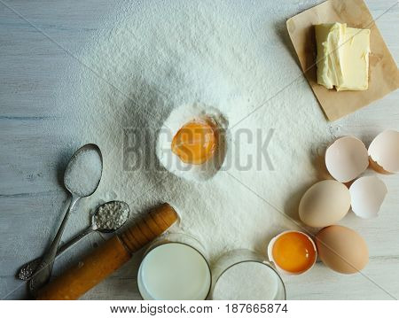Eggs flour milk sugar oil on a white wooden table.