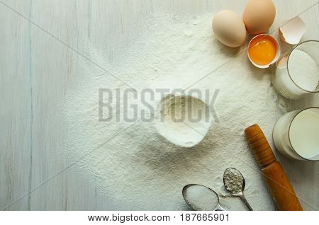 Eggs flour milk sugar oil on a white wooden table. Preparation of ingredients for baking. View from above.