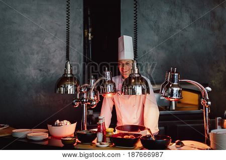 Cook at the buffet in the interior chef cooking at berbecue dinner buffet