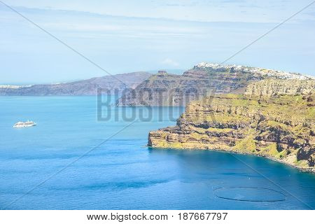 View of the sea and the ship with steep coast of the island of Santorini Greece