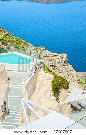 Pool with turquoise water on steep cliff of the Greek island of Santorini against the blue sea