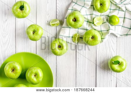 ripe green apples with plate on white table background top view
