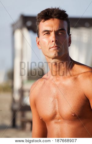 Portrait man shirtless, chest e serious expression. Outdoors. A handsome man with bare chest. He is on the beach without a shirt. Fair and confident attitude. Looking away.