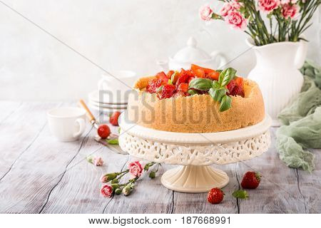 Delicious homemade strawberry cheesecake and flowers on old white wooden background. Selective focus. Copy space.