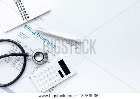 health care costs with billing statement, stethoscope and calculator on white table background top view mockup