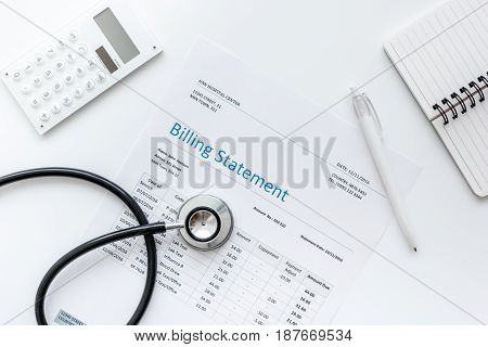 medical treatmant billing statement with stethoscope and calculator on white desk background top view mock up