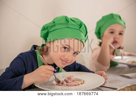 Cheerful girl in cook cap eating meat
