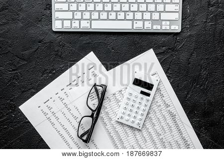 Business report preparing with calculator and glasses on dark office desk background top view