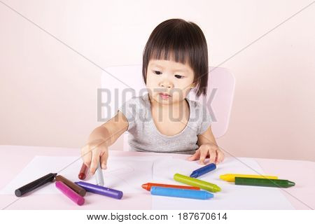 Adorable child drawing with colorful crayons and smiling with the copy space.