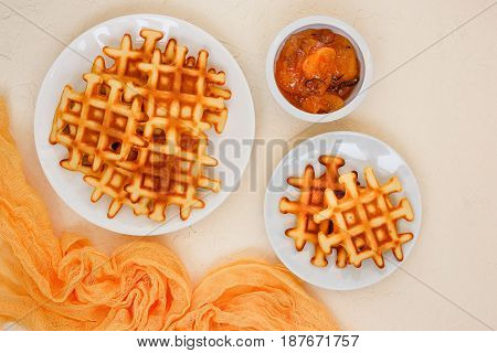 Two plates of Belgian waffles and peach jam with rosemary top view