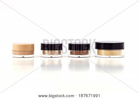 Mineral beauty makeup kit. Plastic jars with foundation powder bronzer concealer highlighter isolated on white