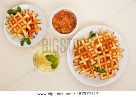 Belgian waffles on plate garnished with mint leaves glass Cup of green tea with mint and peach jam with rosemary in small bowl on beige background. Top view