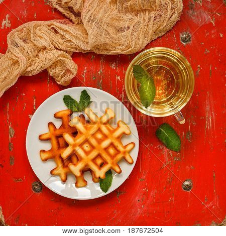 Belgian waffles on plate garnished with mint leaves glass Cup with green tea with mint and peach jam with rosemary in small bowl on red background. Top view