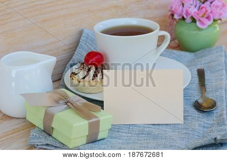 Cup of tea with cute sweet cake roses and box gift greeting card with copy space. Woman morning breakfast surprise concept.