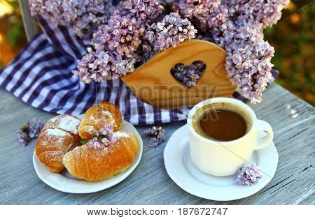 Cup of coffee with croissants and a bouquet of lilacs on the table in the garden