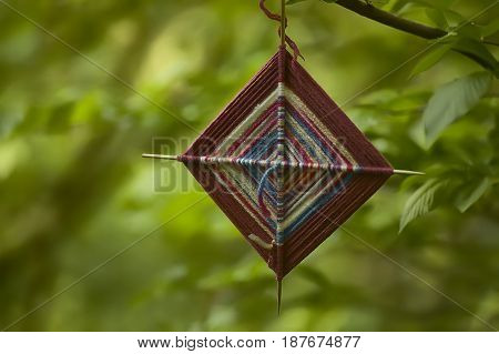 Small spiritual amulet in fabric hanging from a tree at a shamanic ceremony.