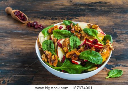 Healthy vegetarian salad with green spinach leaves dried cranberry red apple and walnuts caramelized in honey in a white bowl on the rustic wooden table.