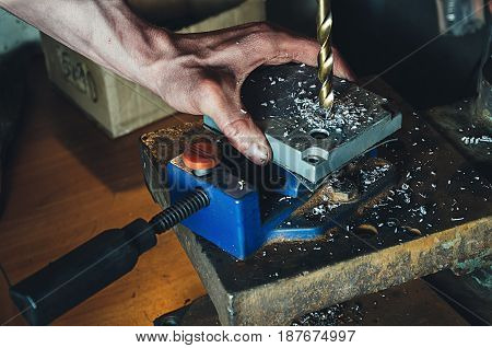 Employee drilling in flat steel plate with bench drill.