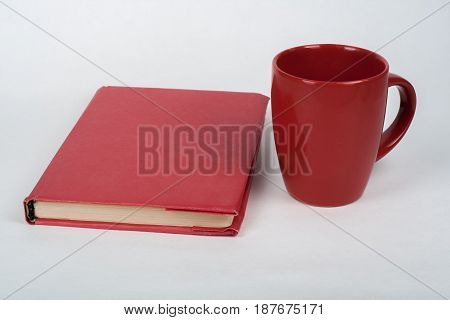 red book and cup on a white table