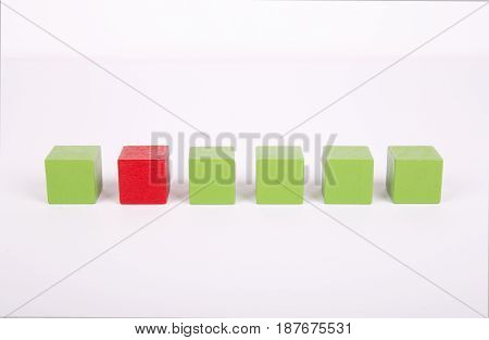 Green and red wooden block in one line represent unique concept.