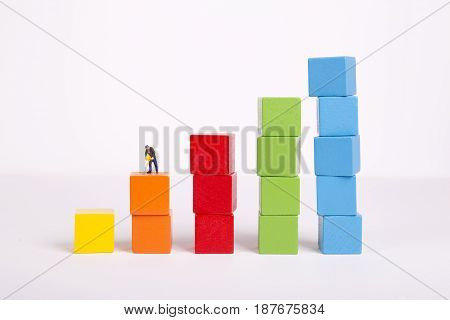 Miniature people on stack of colorful wooden cube building blocks worker digging on colorful wooden cube.