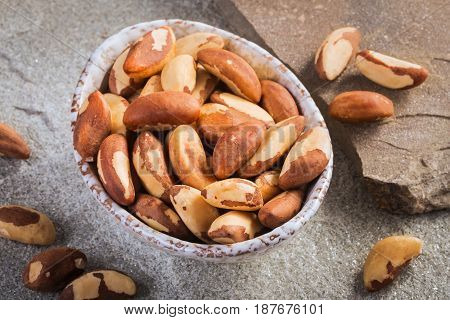 Bowl of peeled brazil nuts on stone background closeup