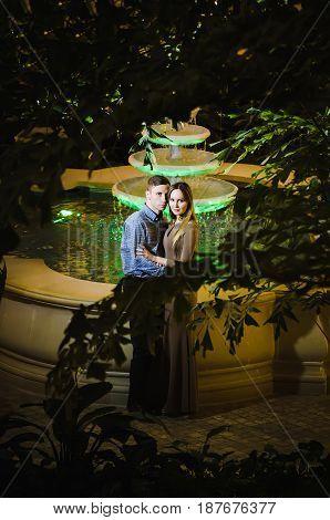 Romantic couple in the tropical jungle near the fountain.