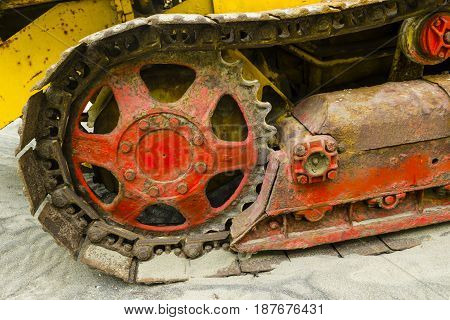 Detail of rusty caterpillar tractor track with sand