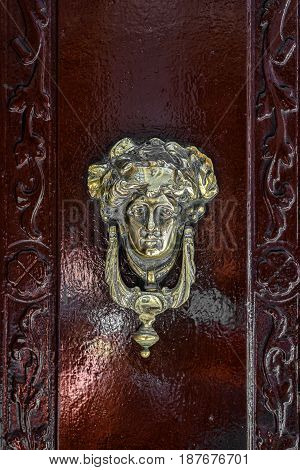 An antique knocker in the shape of a female head on a wooden door.