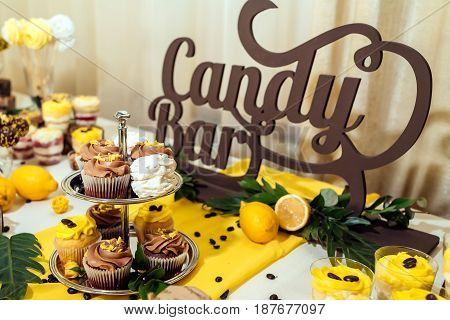 Holiday Candy Bar. Candy Bar Served With Cupcakes With Chocolate And Lemon Cream On Metal Stand