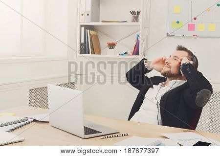 Relaxed businessman enjoy music in headphones in modern white office. Handsome man, happy and successful employee has break at work. Lifestyle portrait