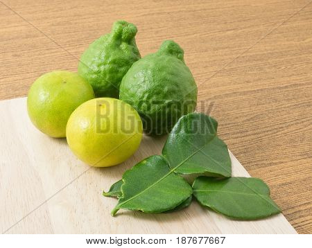 Vegetable and Herb Kaffir Lime with Persian Lime and Kaffir Leaves for Seasoning in Cooking on A Wooden Board.