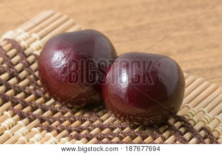 Fresh Fruits Two Ripe and Sweet Red Plums on A Wooden Mat Plate Very Good Source of Vitamin C.